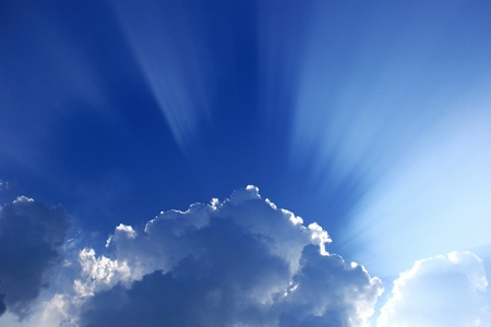 Sun ray behind clouds photo