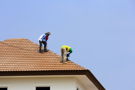 roof top: Workers   repair  concrete  roof  tile on  blue  sky  background Stock Photo