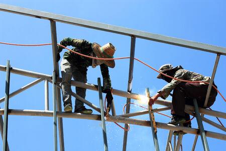 welder welding  metal  on construction site photo