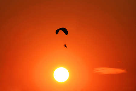 Paramotor flying on sunset  background photo