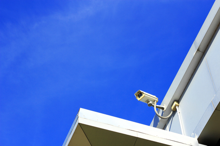 Closed  circuit  television surveillance  camera  on  blue sky background photo