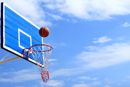Basketball scoring  goal on hoop  with blue sky background