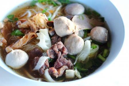 rice noodle soup with sliced rare beef and meat ball photo