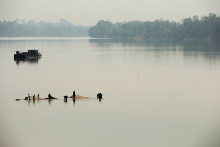 Fishermen move their fishing net from river on early morning   photo