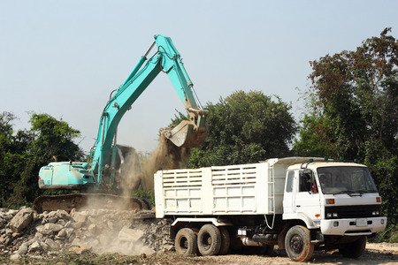 excavator loading stone dump truck on construction site  photo