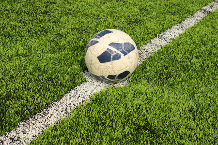 Old soccer ball on artificial turf  in stadium  photo