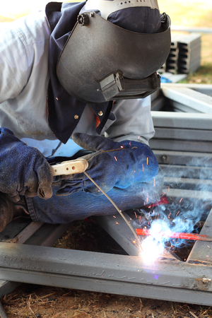 welder welding  metal on construction site  photo