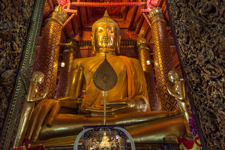 big  golden buddha statue sitting in temple at wat panan choeng temple thailand