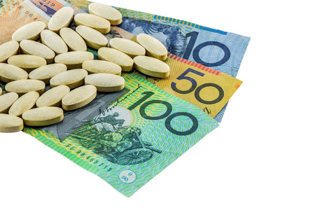 medicine tablets on australia banknotes on white background