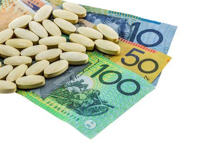medicine tablets on australia banknotes on white background