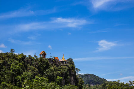thai temple on top of mountain cliff on blue sky background photo