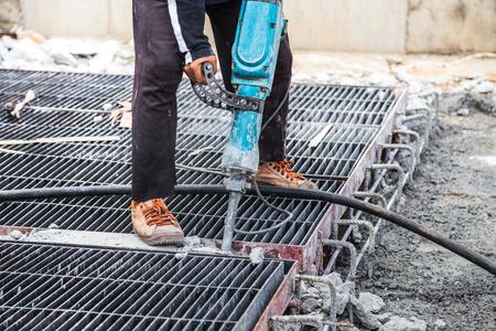 工事現場で削岩機ドリル床セメントを用いた建設労働者 写真素材