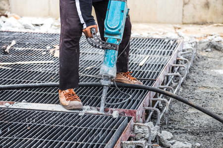 construction worker using  jackhammer drill floor cement on construction site photo