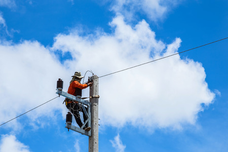 electrician repairing wire of the power line on electric power pole photo