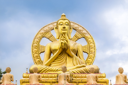big  golden buddha statue sitting with wheel of dhamma background  photo