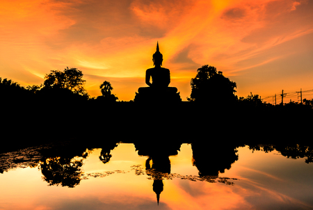 silhouette big buddha statue sitting reflection on the water in sunset