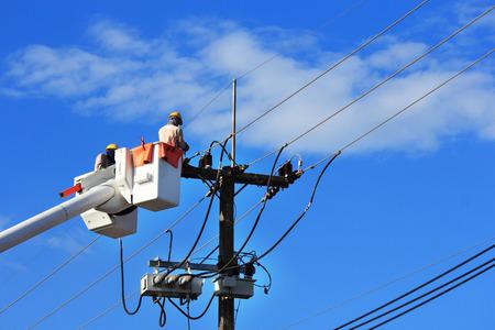 energia electrica: Electricistas en la reparaci�n de alambre de la l�nea el�ctrica en la plataforma hidr�ulica Foto de archivo
