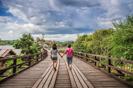 two women holding hands walking together on wooden bridge photo