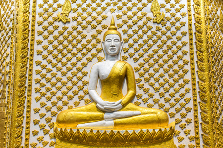 ancient buddha statue sitting on wall pagoda in thai temple photo