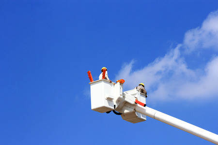 Electricians working on hydraulic platform Stock Photo