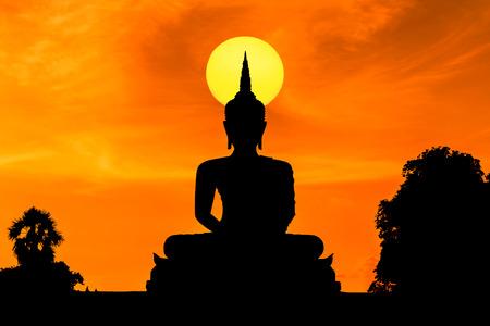 silhouette big buddha statue sitting on sunset 写真素材