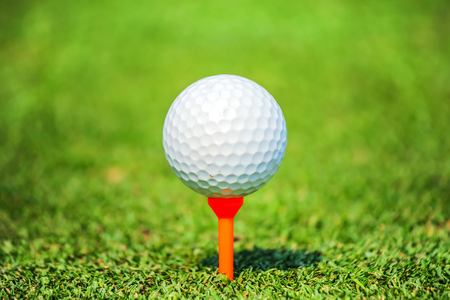 chipping: golf ball with tee on green grass Stock Photo