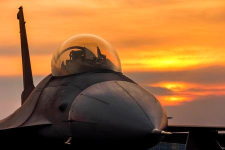 piloto de avion: avión de combate F-16 Falcon en el fondo la puesta del sol Editorial