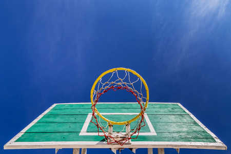 basketball board with  yellow hoop on blue sky background photo