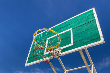 green basketball board with  yellow hoop on blue sky background photo
