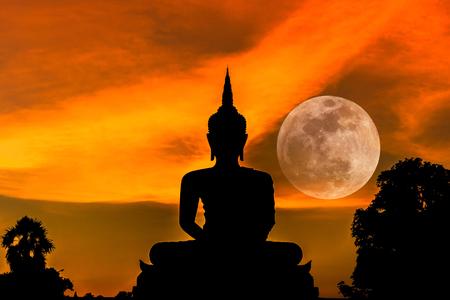 sol y luna: silueta gran estatua de Buda sentado en la puesta del sol con la luna llena de fondo