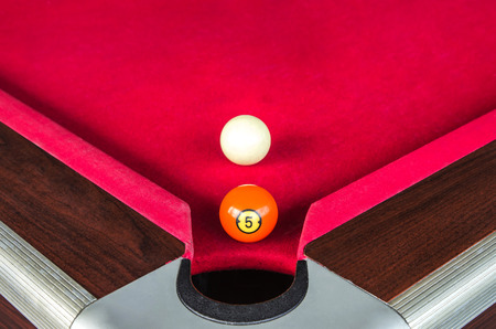 number five: snooker ball five number or pool ball five number near the corner hole with white ball behind