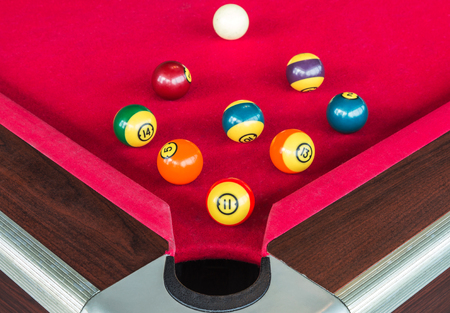 snooker hall: many snooker balls or pool balls near the corner hole on red table