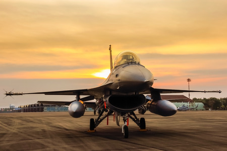 f16 falcon fighter jet parked in the airport  on sunset  background