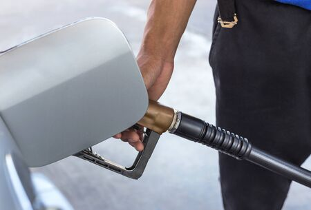 fill up: man hand fill up fuel gas on service station.