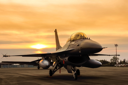 f16 falcon fighter jet parked in the airforce on sunset  background.