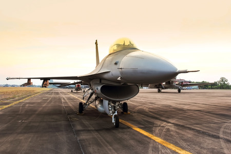 f16 falcon fighter jet parked in the airforce on sunset  background