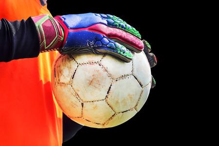 arquero futbol: portero de fútbol que sostiene vieja pelota de fútbol en la mano con guantes en el fondo negro