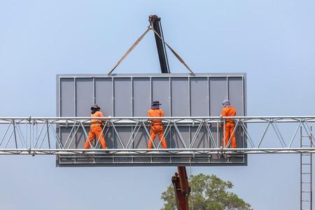 労働者は高速道路に大きな鉄骨看板をインストールします。