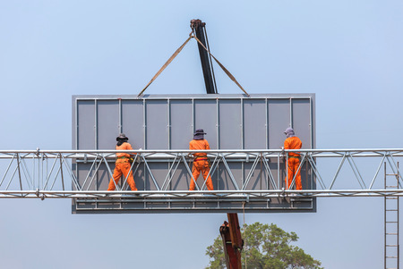 workers install big steel billboard over highway 免版税图像 - 56867792