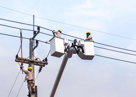 クレーンで電力極の電源線の配線を修復する電気技師