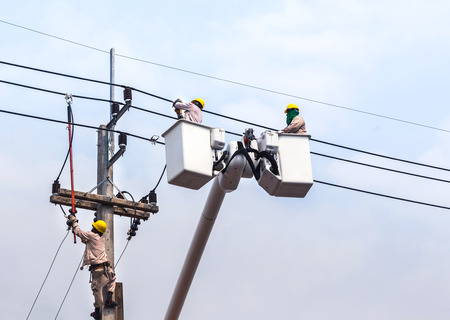 electricians repairing wire of the power line on electric power pole with crane Standard-Bild