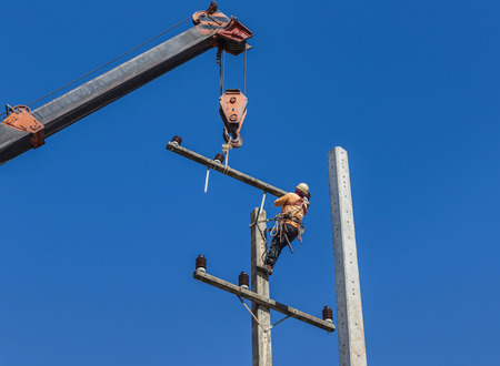 cement pole: electricians repairing wire of the power line on electric power pole with crane Stock Photo
