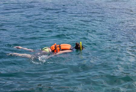 snorkelers: Woman snorkelling in life jacket at andaman sea  phi phi islands, Thailand.