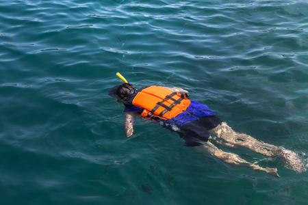 snorkelling: the man snorkelling in the clear tropical turquoise waters in life jacket Stock Photo