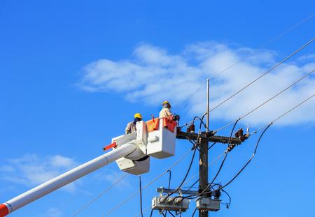 Elektriciens repareren draad van de macht lijn op blauwe hemel achtergrond Stockfoto