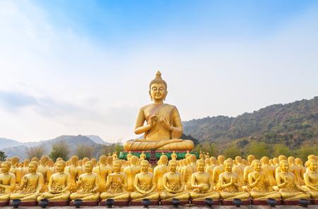 大きな黄金仏像、寺院 nakornnayok タイの行に座っている多くの小さな黄金仏の彫像。 写真素材