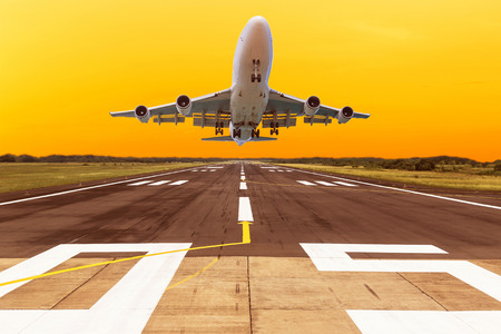 airplane flying take off from runway on sunset