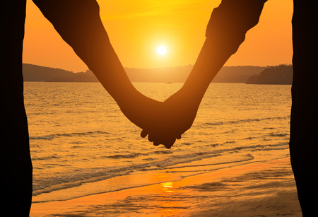 夕日を背景に手を繋いでいるシルエット カップル