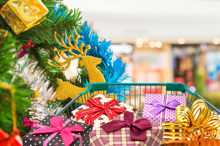 Christmas gifts and presents in shopping trolley cart with christmas decorations and christmas tree background.