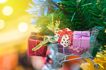 Christmas gifts and presents in shopping trolley cart with christmas tree and blurred lights background. Stock Photo